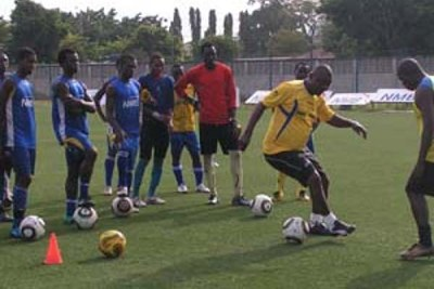 Jamhuri Kihwelu, dribbles as his players and his assistant Mohamed Ayoub (right) look on attentively during a training session.