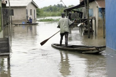 Men canoe to their homes during flooding in Nigeria.