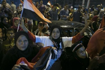Egyptians wave flags during a rally to celebrate the presidential election in Tahrir Square, Cairo.