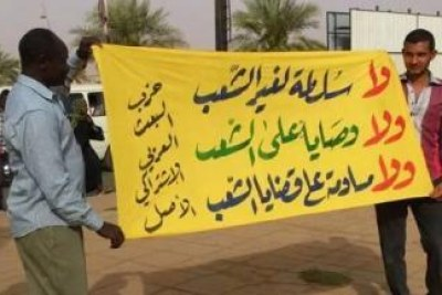"Ba'ath Party members raise a banner reading ""No to power except people's power"" at a protest in Khartoum."
