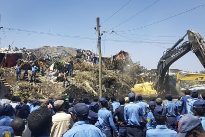 Police officers secure the perimeter at the scene of a garbage landslide, as excavators aid rescue efforts, on the outskirts of the capital Addis Ababa.
