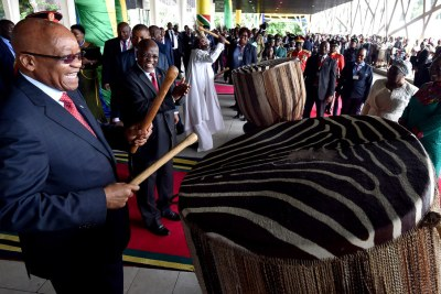 President Zuma beating the traditional drums as President Magafuli looks on.