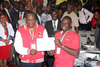 Jubilee party Presidential candidate Uhuru Kenyatta and his running mate William Ruto show their certificate at Kenyatta International Convention Centre on May 29, 2017 after they were cleared by the Independent Electoral and Boundaries Commission.