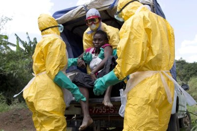 Health workers assist a patient suspected of having Ebola.