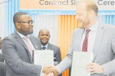 Tanzania Civil Aviation Authority director general Hamza Johari shakes hands with Thales Air Systems regional sales manager Abel Carr after signing an agreement in Dar es Salaam. Looking on is Works, Transport and Communication minister Makame Mbarawa.