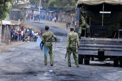 Police officers patrol Kibra streets in Nairobi on August 12, 2017 during protests by residents.