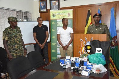 Gashumba (white T-shirt) paraded in front of the press. On the desk are several items like stamps and passports that the army said were used to pursue fraudulent activities.