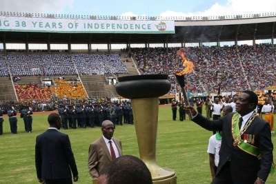 President Emmerson Mnangagwa lights a torch during a celebration marking the nation's 38th independence anniversary.