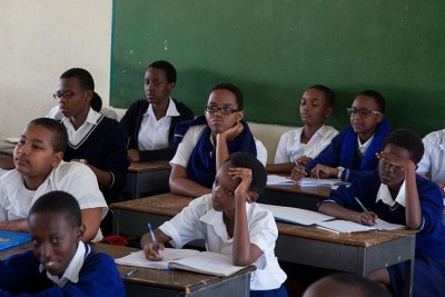 Secondary school students attentively listen to a teacher during a lesson.