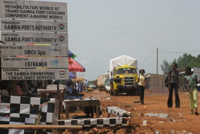 Women walk past a makeshift market on a dirt road at a Transgambia (Senegambia) crossing border town - petit marche en territoire gambien pres de la frontiere senegalo-gambienne