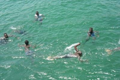 Des enfants jouent dans l'eau de mer sur l'île de Gorée - jeux d'eau sur la plage de Gorée