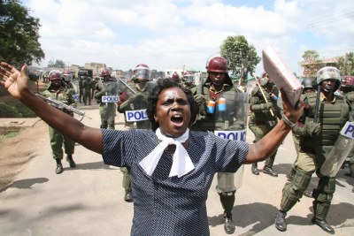 A woman preaches in front of anti-riot police sent to quell the skirmishes that had hit Mathare slums in Nairobi, Kenya.