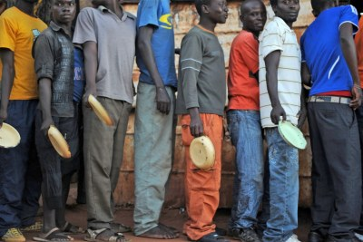 Migrants and asylum seekers at the I believe in Jesus Church shelter for men in the South African border town of Musina queue up for a free hot meal.