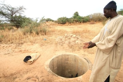 A villager in northern Senegal shows an empty well following poor rains in 2011.