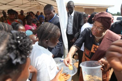 President Sirleaf shares with school children (file photo).