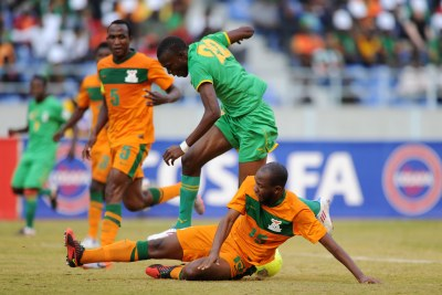 Christopher Munthali of Zambia goes in low to tackle Tendai Ndoro of Zimbabwe during Cosafa Cup in 2013.