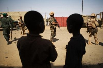 Deux jeunes garçons maliens observent des soldats français. Bamako peine à protéger les enfants qui ont été impliqués dans le récent conflit