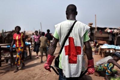 Des volontaires de la Croix-Rouge centrafricaine, en collaboration avec le CICR, nettoient le camp de personnes déplacées de l'aéroport de Bangui