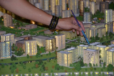 Painting finishing touches onto a model city display of Abuja