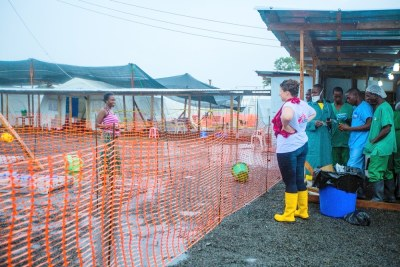 An MSF volunteer speaks from a safe distance with an Ebola patient.