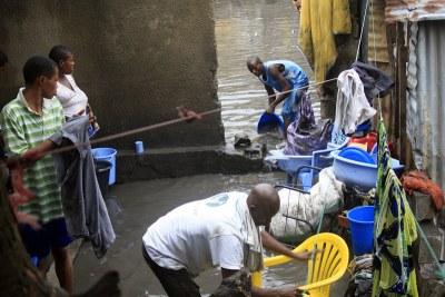 Une famille inondée par les eaux de pluie, tente de récupérer leurs biens en évacuant les eaux stagnantes dans la parcelle.