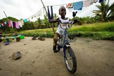 Six-year-old Ebola survivor Patrick Poopei rides his bike in Monrovia.