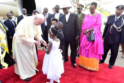 Jasmine Bamwine receives a gift from Pope Francis on his arrival at Entebbe airport.