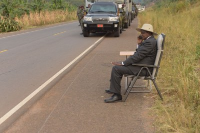 Museveni talking on phone by the roadside.