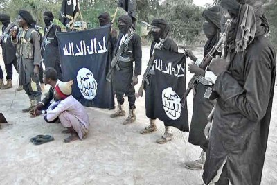 Boko Haram members prepare to cut off the hands of two civilians accused of theft.