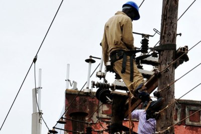 Umeme workers installing a transformer on an old electricity pole in Kampala.