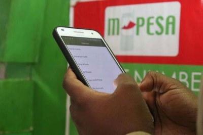 Une personne utilise le service de transfert d'argent M-Pesa.