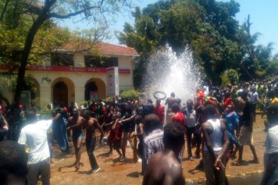 Protestors take bath using water from one of the pipes that were broken by vandals along Oginga-Odinga Street in Kisumu.