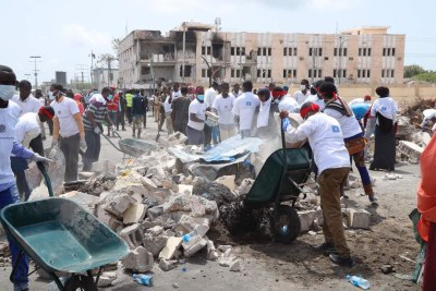 Hundreds of young Somali volunteers arriving at the scene of the explosion to help clean up the debris.
