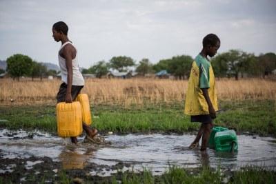 Deux garçons recueillent de l'eau d'un tuyeau endommagé à la périphérie de Juba, au Soudan_du Sud. L'eau est pompée du Nil blanc, mais elle n'est pas traitée, mettant en danger la santé de ceux qui la consomment.
