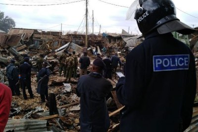 Police officers supervise the demolition of illegal structures in Kibera, Nairobi on July 23, 2018.
