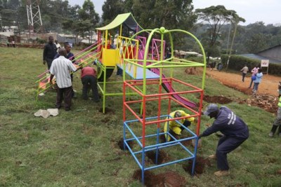 Workmen install equipment at a children's playground rehabilitated from an illegal dumping site in a section of Kangemi area cemetery.