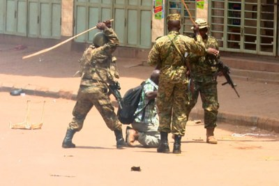 Ugandan soldiers beating up Reuters photojournalist James Akena as he covered the protests over the detention of several Opposition MPs in Kampala (file photo0.