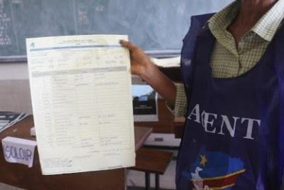 Un agent de la CENI présente la fiche des résultats du comptage manuel des bulletins d'un bureau de vote le 31/12/2018 après le vote organisé le 30 décembre en RDC