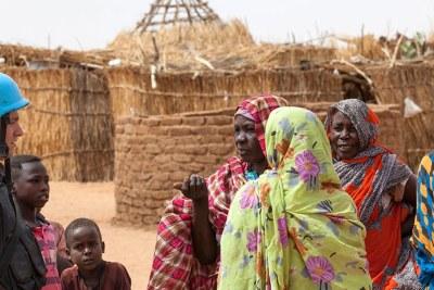 Un officier jordanien de la MINUAD discute avec des résidents du camp de Zam Zam pour déplacés, au Darfour, en 2015.