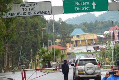 Border check. A Rwandan security officer inspects a vehicle from the Ugandan side at Cyanika border post.