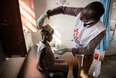 Un membre du personnel MSF examine une jeune fille blessée à la tête dans l'hôpital d'Ulang, dans le nord-est du Soudan du Sud. 2019.