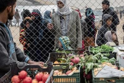 Un marchant ambulant vend des produits alimentaires à l'extérieur d'un camp pour personnes déplacées