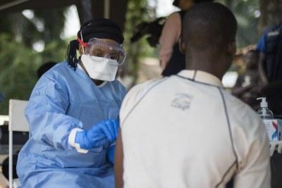 Un membre de l'OMS vaccine un homme contre le virus Ebola dans le village de Bosolo, en RDC.
