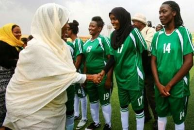 La nouvelle ministre soudanaise des Sports, Wala Essam (R), accueille les joueuses de Tahadi avant le match de la Ligue de football féminine soudanaise opposant Tahadi et Difanin, à Khartoum, la capitale, le 30 septembre 2019.