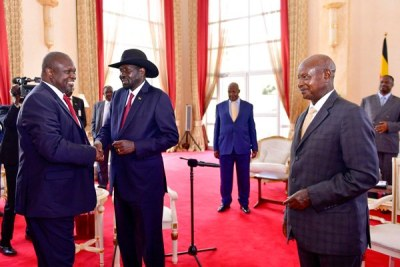 South Sudan's Salva Kiir and Riek Machar interact as President Museveni looks on at State House Entebbe.