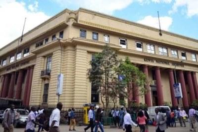 Residents of Nairobi walk past the Kenya National Archives National in Nairobi (file photo).