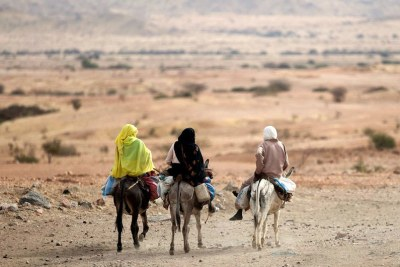 On the outskirts of El Fasher in North Darfur, women ride donkeys on the road to Khartoum, Sudan.