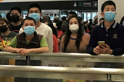 People wear face masks as they wait at China's Shenzhen Bao'an International Airport arrivals.