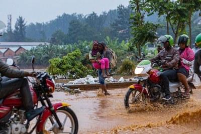 Les gens ont du mal à naviguer sur une route inondée. Les fortes pluies des derniers jours ont causé la mort de 19 personnes et endommagé de nombreux biens.