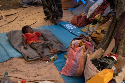 A young Ethiopian refugee sleeps on a mattress at a transit site in Hamdayet, Sudan.